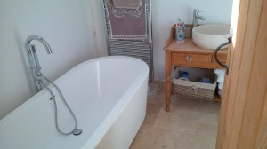 newly installed free standing bath and altered dresser turned vanity unit. (travertine floor tiles)